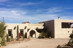 large off-white home with windows and striking Southwestern architecture, pet friendly vacation home for rent in tucson