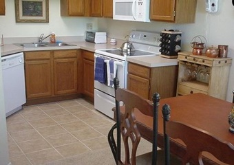 kitchen with wooden cabinets and dining table, stove, muicrowave, double sink, cabinet with glasses, dishwasher, tucson pet friendly vacation rental home