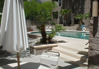 outdoor pool area with palm trees surrounding the pool on the white deck with stair and a railing, white patio furniture and umbrellas, stucson pet friendly vacation rental home